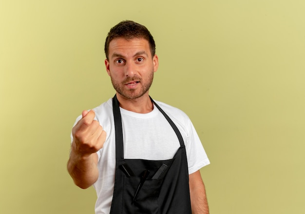 Barber man in apron looking to the front rubbing fingers asking for money standing over light wall