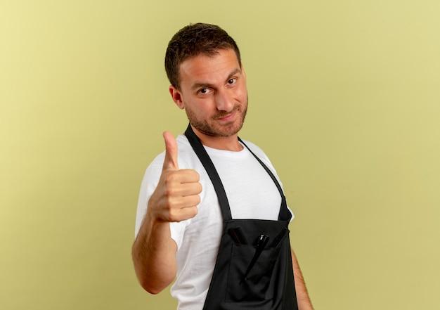Uomo del barbiere in grembiule che guarda al fronte sorridente che mostra i pollici in su in piedi sopra la parete chiara