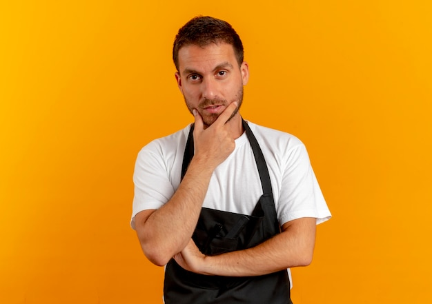 Barber man in apron looking to the front with hand on chin thinking standing over orange wall 2