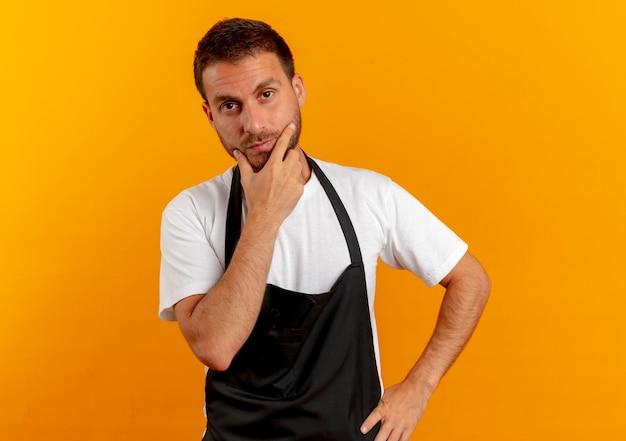 Barbiere uomo in grembiule guardando in avanti con la mano sul mento pensando in piedi sopra la parete arancione