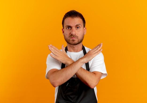 Uomo del barbiere in grembiule guardando in avanti con la faccia seria che fa il gesto di arresto che attraversa le mani in piedi sopra la parete arancione