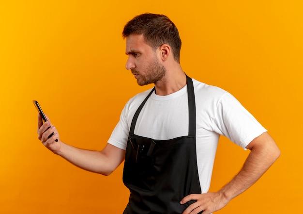 Uomo del barbiere in grembiule guardando lo schermo del suo telefono cellulare con la faccia seria in piedi sopra la parete arancione