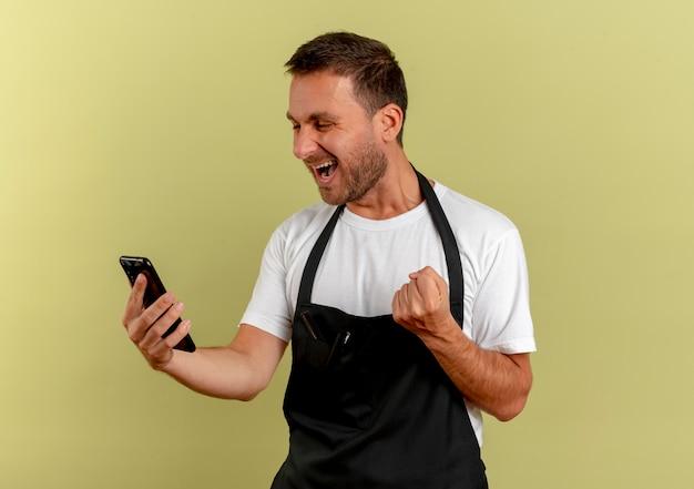 Uomo del barbiere in grembiule che guarda lo schermo del suo pugno di serraggio smartphone felice ed eccitato in piedi sopra la parete chiara