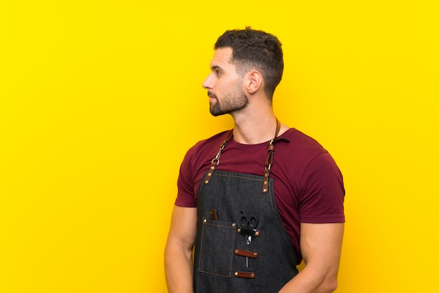 Barber man in an apron looking to the side