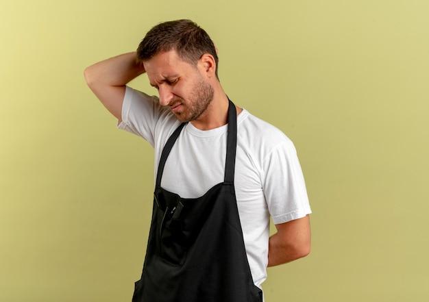 Uomo del barbiere in grembiule alla ricerca di malessere toccando la schiena sensazione di dolore in piedi sopra la parete leggera