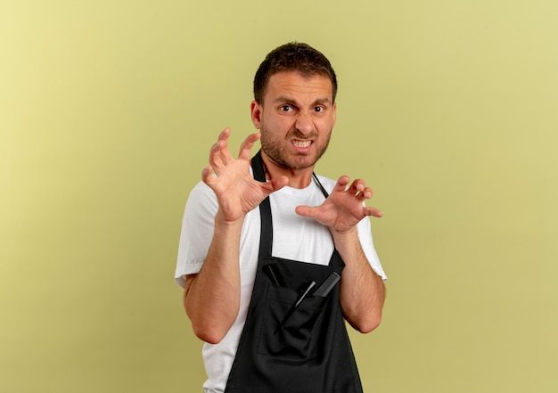 Barber man in apron making defense gesture with hands with disgusted expression standing over light wall