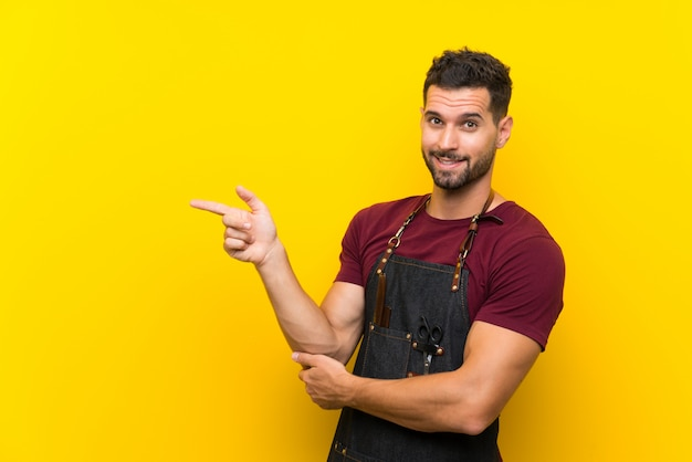 Barber man in an apron pointing finger to the side
