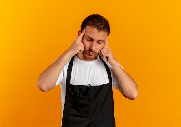 Barber man in apron pointing his temples looking tired and bored standing over orange wall