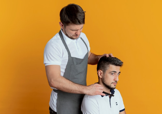 Uomo del barbiere in grembiule da barba con il rasoio del cliente soddisfatto su sfondo arancione