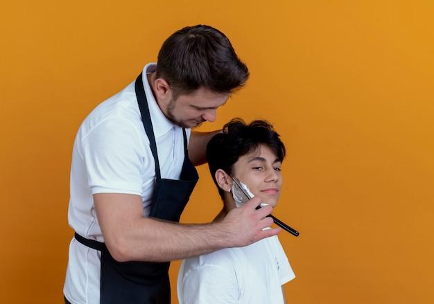Uomo barbiere in grembiule da barba con il rasoio del cliente soddisfatto sopra il muro arancione