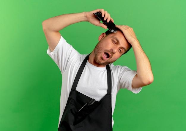 Uomo del barbiere in grembiule che si rade i capelli con la macchina per il taglio dei capelli guardando fiducioso in piedi sopra il muro verde
