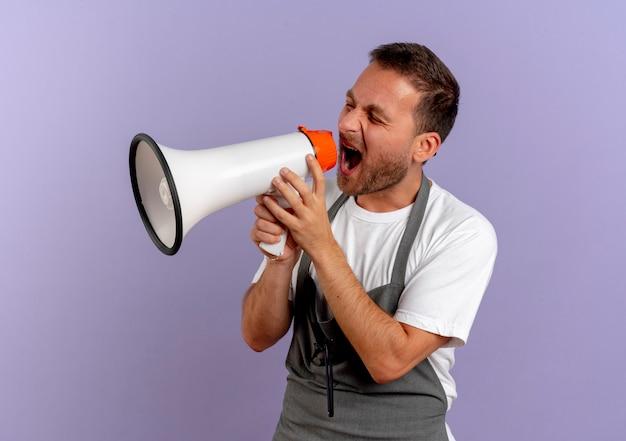Uomo del barbiere in grembiule che grida al megafono con espressione aggressiva in piedi sopra la parete viola