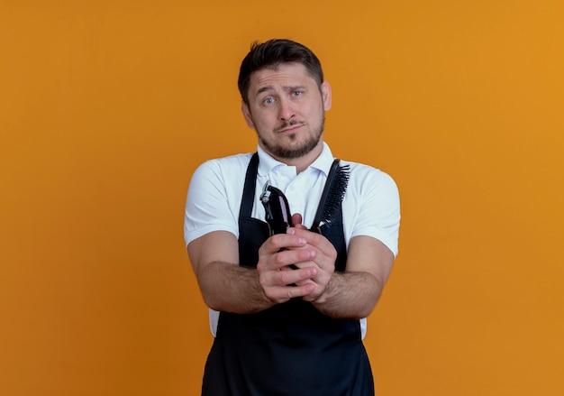 Uomo del barbiere in grembiule che mostra il rifinitore per barba e spazzola per capelli guardando la fotocamera a mendicare con espressione di speranza in piedi su sfondo arancione
