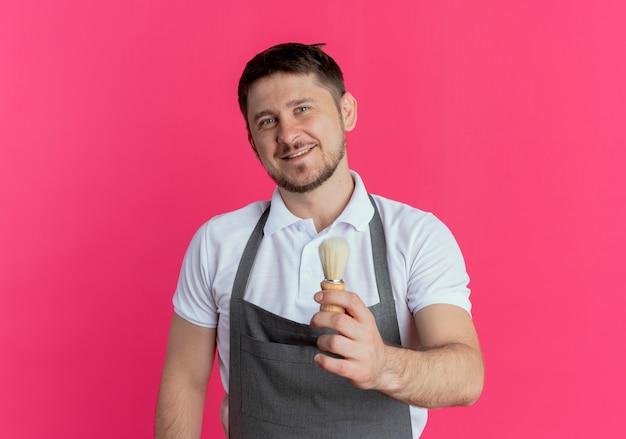 Barbiere uomo in grembiule che mostra il pennello da barba lookign in telecamera con il sorriso sul viso in piedi su sfondo rosa