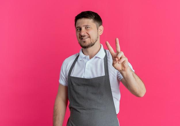 Uomo del barbiere in grembiule sorridente allegramente guardando la telecamera che mostra il segno di vittoria in piedi su sfondo rosa
