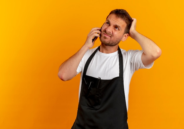 Barber man in apron talking on mobile phone looking displeased standing over orange wall