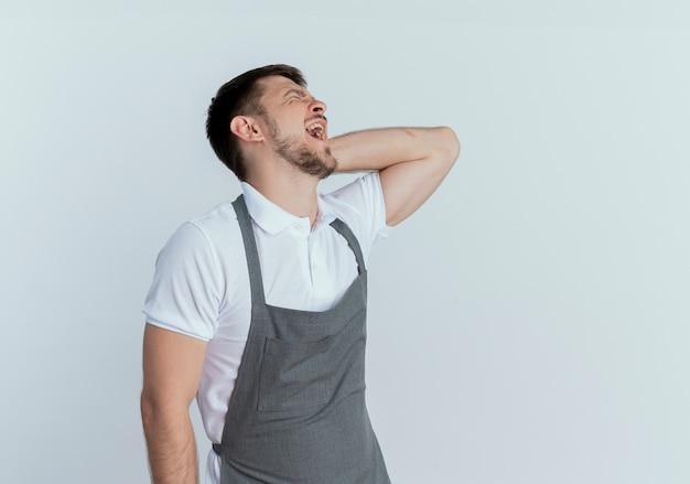 Uomo barbiere in grembiule toccando il collo che sembra malato soffre di dolore in piedi sopra il muro bianco