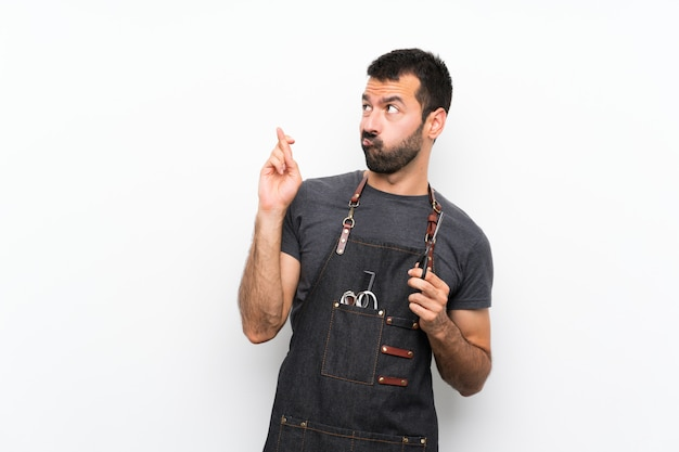 Barber man in an apron with fingers crossing and wishing the best