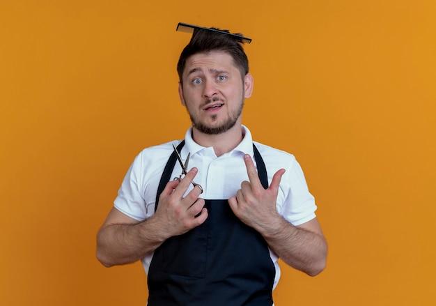 Barbiere uomo in grembiule con spazzola per capelli tra i capelli tenendo le forbici guardando la telecamera confusa in piedi su sfondo arancione