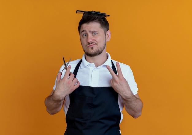 Barbiere uomo in grembiule con spazzola per capelli tra i capelli tenendo le forbici che mostra il numero due guardando la telecamera scontento in piedi su sfondo arancione