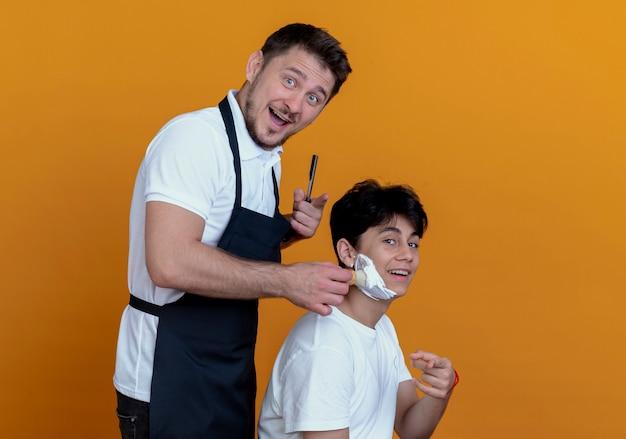 Barbiere uomo in grembiule con faccia felice puntando il dito mettendo la schiuma da barba con pennello da barba sulla faccia del cliente soddisfatto sulla parete arancione