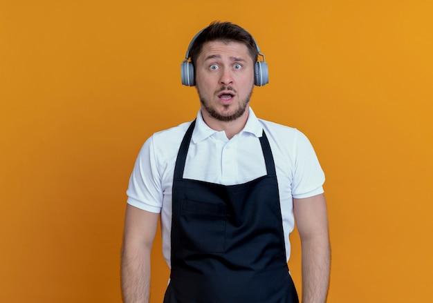 Uomo del barbiere in grembiule con le cuffie che guarda l'obbiettivo in piedi confuso e molto ansioso su sfondo arancione