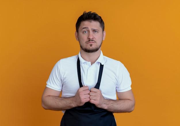 Uomo barbiere in grembiule con espressione triste in piedi sopra il muro arancione