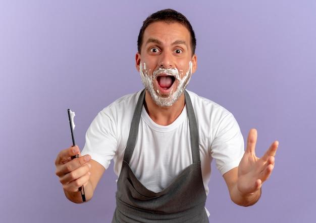 Uomo del barbiere in grembiule con schiuma da barba sul viso che tiene il rasoio guardando in avanti sorpreso e felice in piedi sopra il muro viola