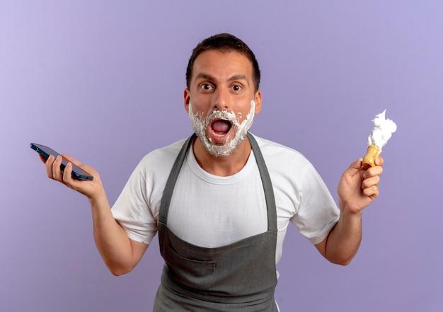 Uomo del barbiere in grembiule con schiuma da barba sul viso che tiene smartphone e pennello da barba guardando sorpreso e stupito in piedi sopra il muro viola 2
