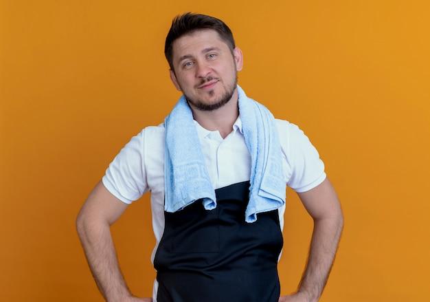 Barbiere uomo in grembiule con asciugamano intorno al collo lookign in telecamera sorridente fiducioso in piedi su sfondo arancione