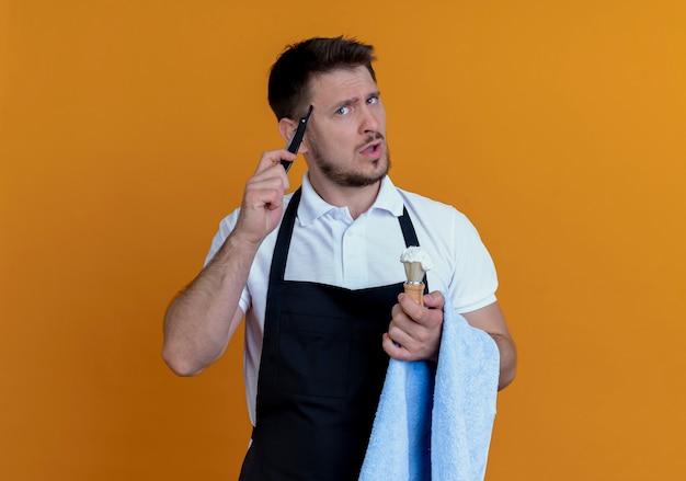 Barbiere uomo in grembiule con asciugamano sulla sua mano tenendo il pennello da barba con schiuma e rasoio guardando la telecamera perplesso in piedi su sfondo arancione