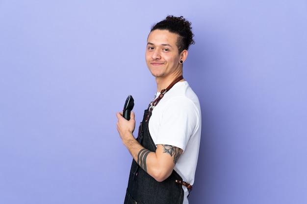 Парикмахер в фартуке над изолированным фиолетовым смехом