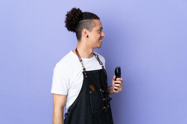 Парикмахер в фартуке над изолированной фиолетовой стороной