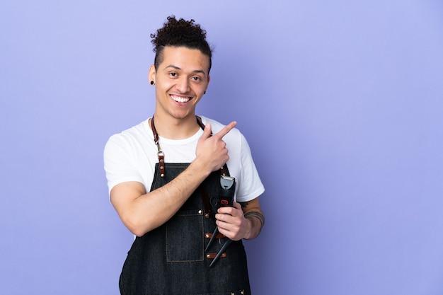 Парикмахер в фартуке над изолированным фиолетовым указательным пальцем в сторону