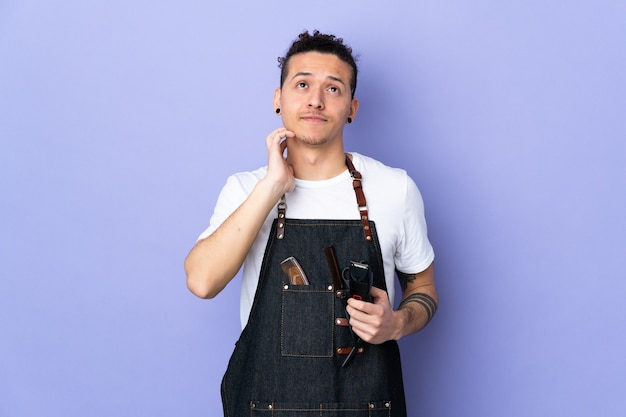 Парикмахер в фартуке над изолированной фиолетовой стеной, думая об идее