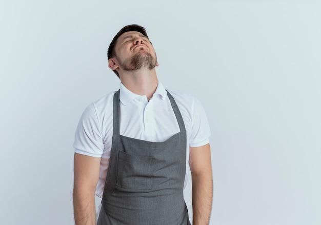 Мужчина-парикмахер в фартуке обеспокоен и устал, закрывая глаза с раздраженным выражением лица, стоя на белом фоне