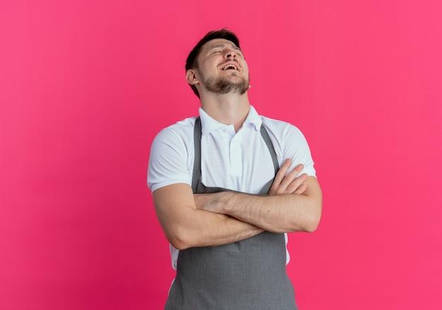 Парикмахер в фартуке обеспокоен и устал со скрещенными руками, стоя на розовом фоне