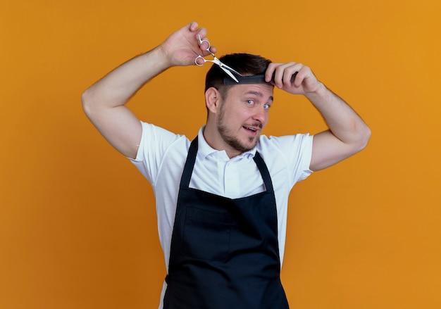 Парикмахер в фартуке, расчесывающий и стригущий волосы, стоя на оранжевом фоне