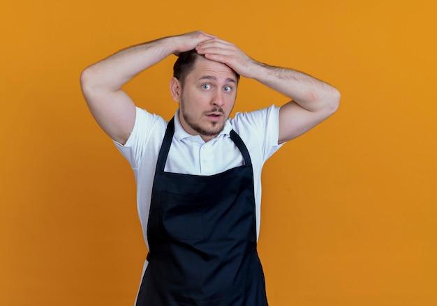 Парикмахер в фартуке расчесывает волосы и выглядит удивленным, стоя на оранжевом фоне Бесплатные Фотографии