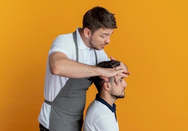 Парикмахер в фартуке стрижет ножницами волосы довольного клиента над оранжевой стеной
