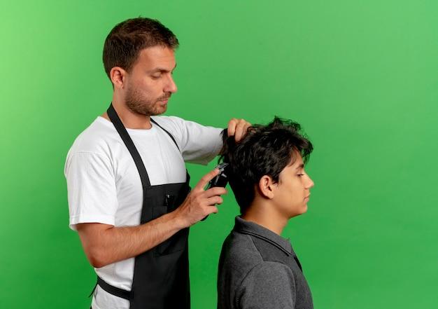 緑の壁の上に立っている満足しているクライアントのトリマーで髪を切るエプロンの理髪師