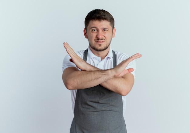 エプロンの床屋の男は、白い壁の上に立っている手を交差させる一時停止の標識を示すことに不満を持っています