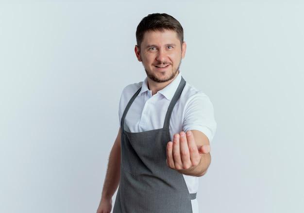 Парикмахер в фартуке делает жест с рукой, дружелюбно улыбаясь, стоя над белой стеной