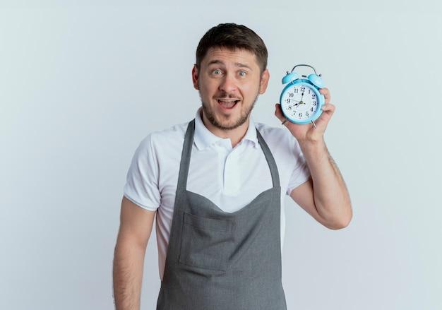 白い背景の上に立って幸せと驚きのカメラを見て目覚まし時計を保持しているエプロンの理髪店の男