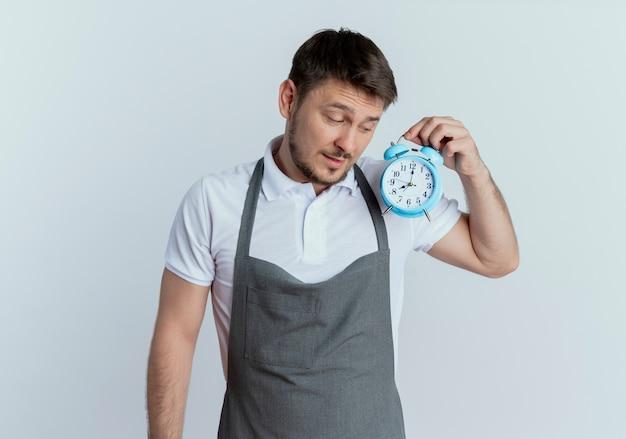 白い壁の上に立っている真面目な顔でそれを見ている目覚まし時計を保持しているエプロンの床屋の男