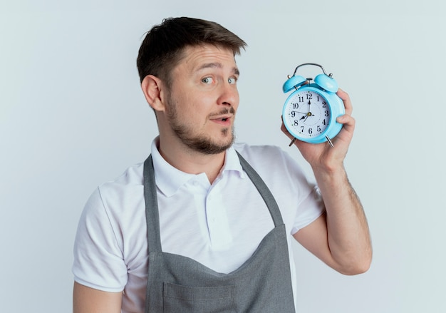 白い壁の上に立っている顔に懐疑的な笑顔で目覚まし時計を保持しているエプロンの床屋の男
