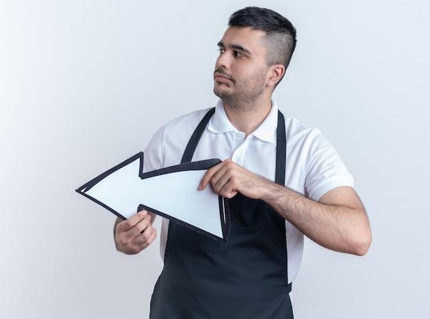 白い背景の上に立っている深刻な顔で脇を見て矢印を保持しているエプロンの理髪店の男