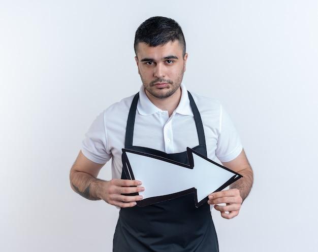 白い背景の上に立っている真剣な自信を持って表情でカメラを見て矢印を保持しているエプロンの理髪店の男