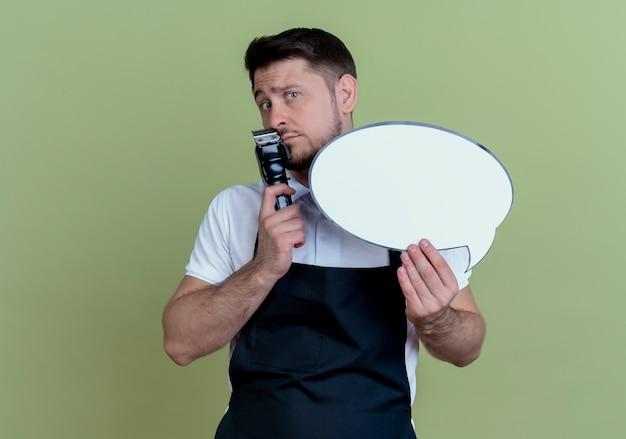 Парикмахер в фартуке с триммером для бороды и пустым речевым пузырем озадаченно стоит над зеленой стеной