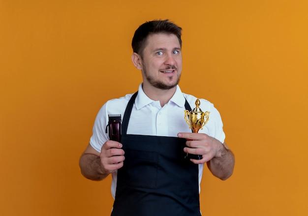 オレンジ色の壁の上に立っている幸せそうな顔で笑顔のひげトリマーとトロフィーを保持しているエプロンの理髪店の男